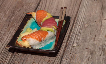 Dragon roll sushi with salmon, tuna, avocado, shrimp tempura and rice on a plate with chopsticks