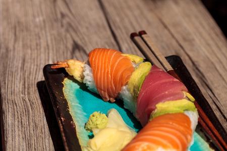 Dragon roll sushi with salmon, tuna, avocado, shrimp tempura and rice on a plate with chopsticks Stock Photo - 63998705