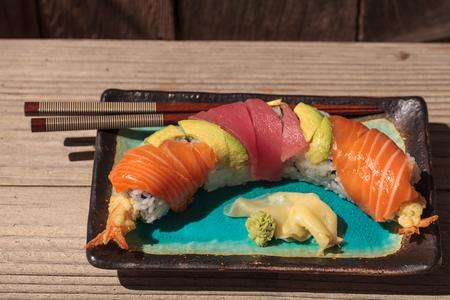 Dragon roll sushi with salmon, tuna, avocado, shrimp tempura and rice on a plate with chopsticks Stock Photo - 63998801