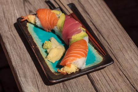 Dragon roll sushi with salmon, tuna, avocado, shrimp tempura and rice on a plate with chopsticks Stock Photo - 63998806