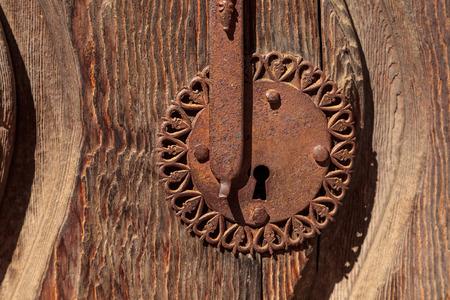 Ornate Rusty door keyhole on rustic distressed wood background