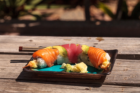 Dragon roll sushi with salmon, tuna, avocado, shrimp tempura and rice on a plate with chopsticks Stock Photo - 63999065