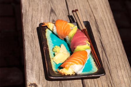 Dragon roll sushi with salmon, tuna, avocado, shrimp tempura and rice on a plate with chopsticks Stock Photo - 63999123
