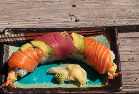 Dragon roll sushi with salmon, tuna, avocado, shrimp tempura and rice on a plate with chopsticks Stock Photo - 63999122