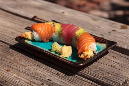 Dragon roll sushi with salmon, tuna, avocado, shrimp tempura and rice on a plate with chopsticks Stock Photo - 63999127