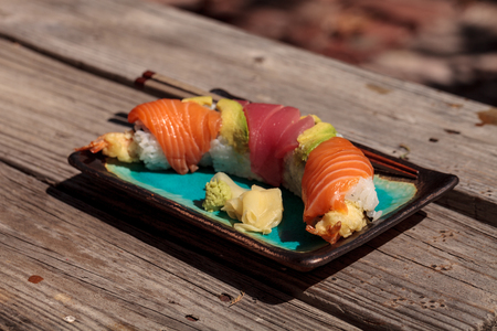 Dragon roll sushi with salmon, tuna, avocado, shrimp tempura and rice on a plate with chopsticks Stock Photo - 63999018