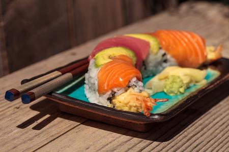 Dragon roll sushi with salmon, tuna, avocado, shrimp tempura and rice on a plate with chopsticks Stock Photo - 63999025