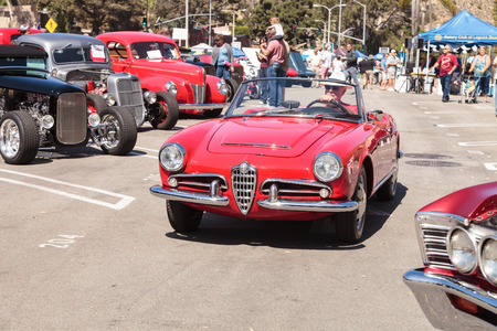 romeo: Laguna Beach, CA, USA - October 2, 2016: Man drives a red classic Alfa Romeo Milano car out of the Rotary Club of Laguna Beach 2016 Classic Car Show. Editorial use.
