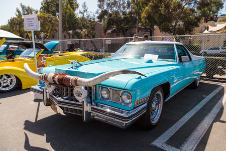 caddie: Laguna Beach, CA, USA - October 2, 2016: Blue 1973 Cadillac Caribou with steer horns owned by Maverick Nehemiah and displayed at the Rotary Club of Laguna Beach 2016 Classic Car Show. Editorial use. Editorial