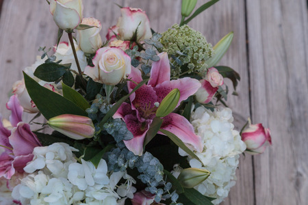 gazer: Wedding bouquet of white and pink flowers including roses, hydrangea, star gazer lilies and queen annes lace on a rustic table in the French countryside on Valentine�s Day