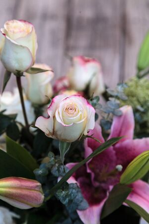 gazer: Wedding bouquet of white and pink flowers including roses, hydrangea, star gazer lilies and queen annes lace on a rustic table in the French countryside on Valentine's Day