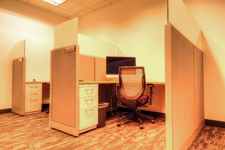 Office cubicle sits empty in an office building 스톡 콘텐츠