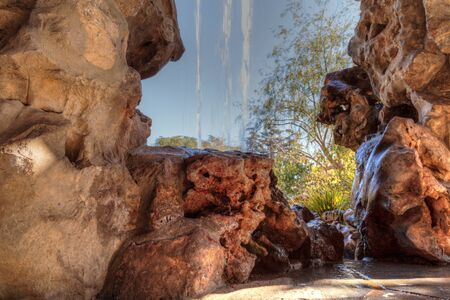 Waterfall flows over a manmade rock structure in a garden