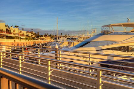 Balboa Island harbor at sunset with ships and sailboats visible from the bridge that leads into Balboa Island, Southern California, USA Stock Photo