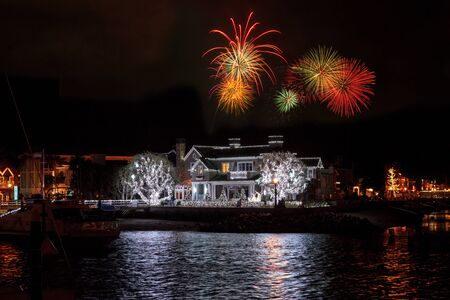Fireworks over colorful holiday lights on a home and on sailboats and ships in the Balboa Harbor for the Newport Beach Christmas Boat Parade.