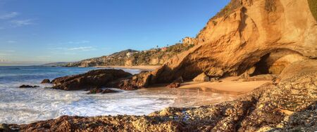 Blue sky over the coastline of One Thousand Steps Beach with tidal pools and cliffs in Laguna Beach, California, USA