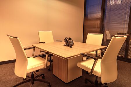 Small corporate conference room with a table and four chairs around a conference bridge phone in a professional building. Zdjęcie Seryjne