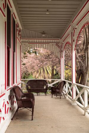 porch scene: Los Angeles, CA, USA � January 15, 2017: Red and white porch of a Victoria cottage with pink flowers in bloom on a tree at the Los Angeles Arboretum in Southern California. Editorial use.