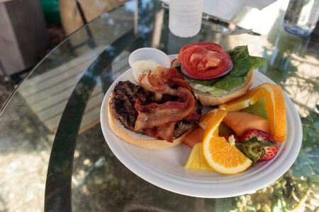 Hamburger with bacon on top on a fluffy bread bun and a side of fruit including oranges, strawberries, melon and pineapple for lunch.