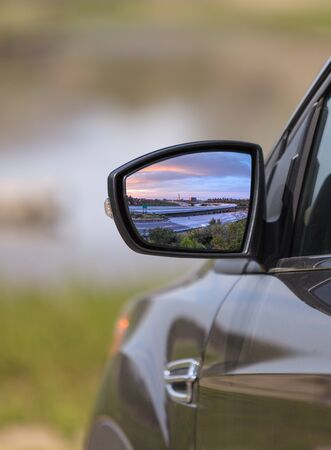 Sunset over a California highway in the rear view mirror of a car in summer on a road trip