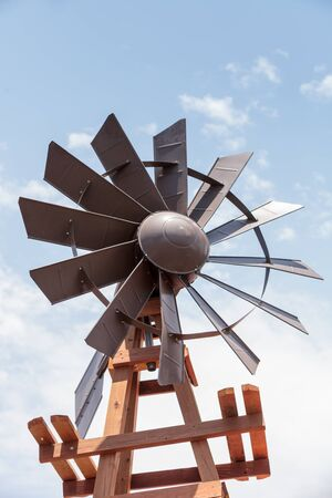 Metal windmill against a blue sky on a farm in summer Imagens - 82178123