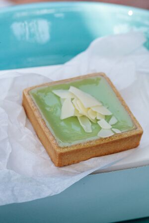 junk: Green Keylime tart pastry with a cookie crust and white chocolate flakes in bakery. Stock Photo
