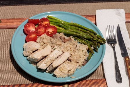 Sauteed pork and asparagus with mushroom risotto meal on a rustic dinner plate