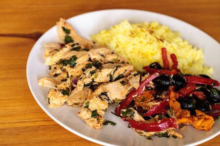 Spicy Chicken Diablo with cilantro, olives, peppers, garlic and onion served over saffron yellow rice. Stock Photo