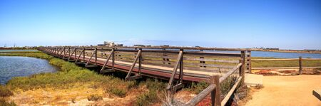 Bridge along the peaceful and tranquil marsh of Bolsa Chica wetlands in Huntington Beach, California, USA Stock Photo