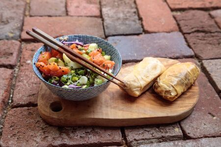 Raw salmon poke bowl with rice, cabbage, cucumber, sesame seeds and spring rolls with chopsticks. Stock Photo