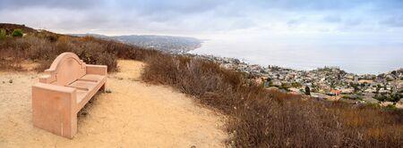 joaquin: Dark rain clouds over a bench that overlooks the coastline of Laguna Beach, California, from the Laguna Coast Wilderness Park in summer. Stock Photo