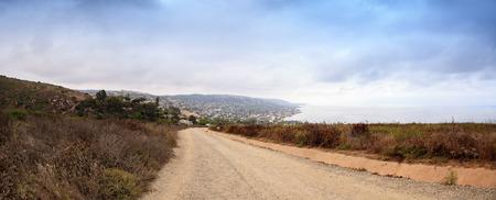 joaquin: Dark rain clouds over the coastline of Laguna Beach, California, from the Laguna Coast Wilderness Park in summer.