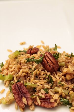 Healthy pecan nut brown rice with cilantro and spices on a white plate Stock Photo