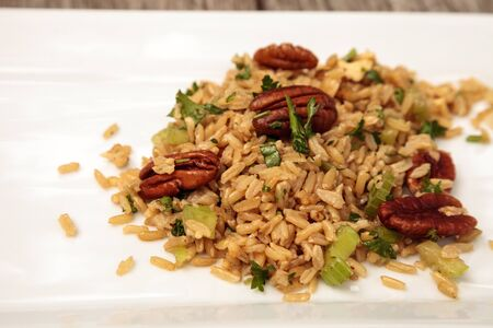 Healthy pecan nut brown rice with cilantro and spices on a white plate 版權商用圖片