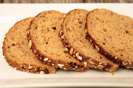Brown multigrain bread slices on a white plate