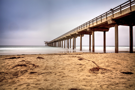 Overcast cloudy day over Scripps pier Beach in La Jolla, California at the end of Summer Stock Photo