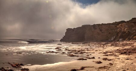Fog drifts in over the ocean at Crystal Cove state beach on the edge of Laguna Beach and Corona del Mar, California in fall. Stock Photo
