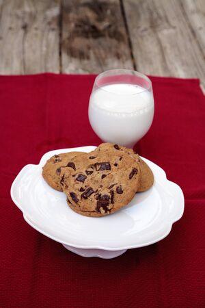 빨간 식탁보에 유리에 전체 우유와 함께 하얀 접시에 초콜릿 칩 쿠키