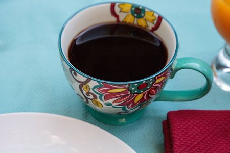 Black coffee in a colorful flower print cup with orange juice on a blue table cloth