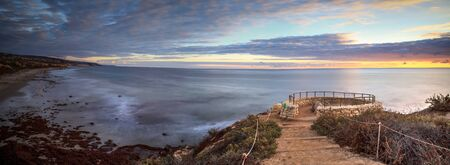 Sunset in a stone overlook that views Crystal Cove State Park Beach in Fall near Newport Beach, California