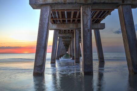 On the beach under the Naples Pier at sunset in Naples, Florida, USA