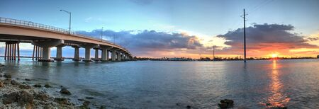 Sunset over the bridge roadway that journeys onto Marco Island, Florida over the bay. Archivio Fotografico