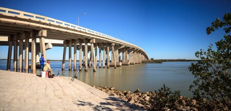 Blue sky over the bridge roadway that journeys onto Marco Island, Florida over the bay.