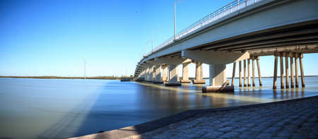 Blue sky over the bridge roadway that journeys onto Marco Island, Florida over the bay. Stock Photo