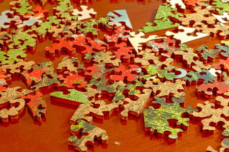 Puzzle pieces spread across a dark wood table in fragments as they wait for assembly. Stock Photo