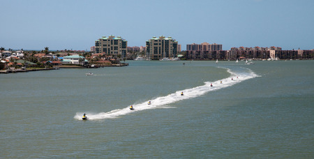Skyline in the background as a Group of jet skies zip along the ocean in a straight line, making waves in the ocean in the bay in front of Marco Island, Florida Archivio Fotografico