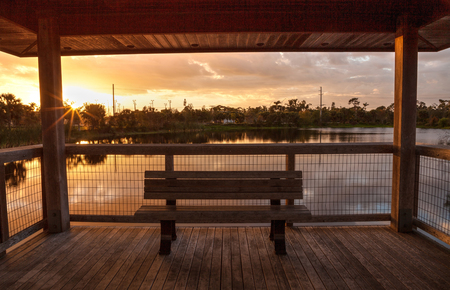 Sunset Wooden bench on a secluded, tranquil boardwalk along a marsh pond in Freedom Park in Naples, Florida Фото со стока