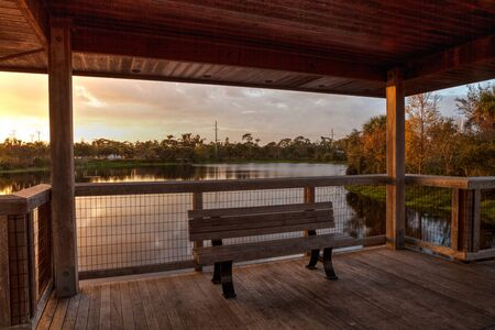 Sunset Wooden bench on a secluded, tranquil boardwalk along a marsh pond in Freedom Park in Naples, Florida Reklamní fotografie