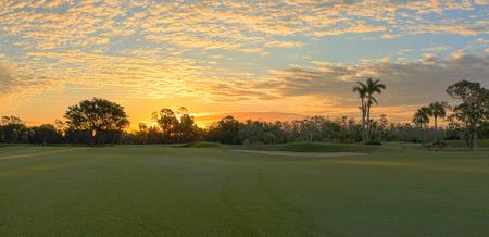 カラフルな日の出空を持つ熱帯ゴルフコースの夜明けに緑の草を刈りたての。