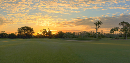 Freshly mowed green grass at dawn on a tropical golf course with a colorful sunrise sky.